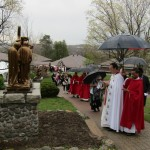 Fr Michael prays at the first station of the cross, crowd lines-up behind him.