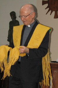 Fr. Bernie Carroll examines the handmade deerskin stole presented to him by the Board of Trustees